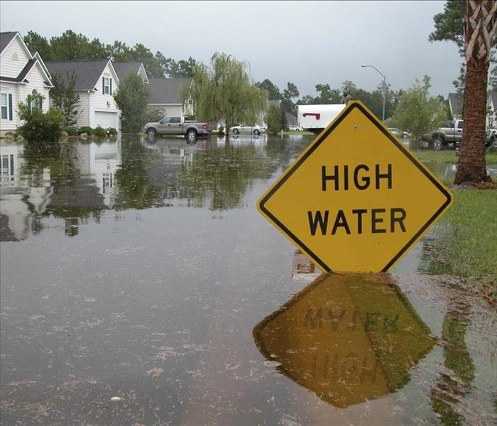 High water yellow sign with flooded roads and homes in background