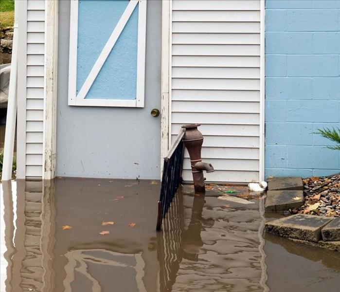 Outside a the back of a house dark brown floodwater is halfway up the basement door